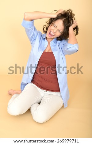 Attractive Young Woman Sitting on the Floor Wearing a Blue Shirt and White Jeans Having a Temper Tantrum Pulling Her Hair - stock photo
