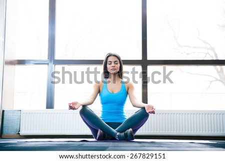 Attractive young woman sitting on yoga mat and meditating at gym - stock photo