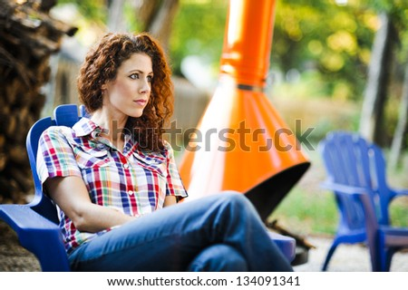 attractive young woman sitting outside - stock photo