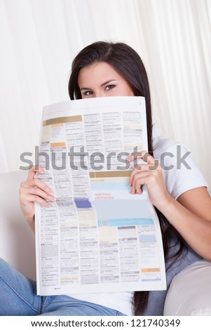Attractive young woman sitting relaxing on a couch reading a newspaper with a cheerful smile - stock photo