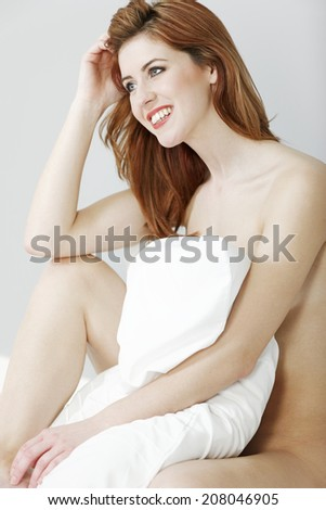 Attractive young woman sitting up in her bed holding a white pillow.