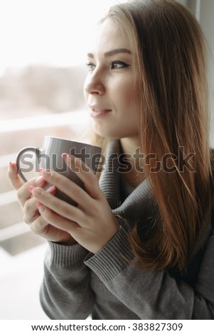 Attractive young woman sitting with coffee at window