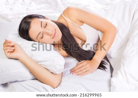 Attractive young woman sleeping in white bed - stock photo