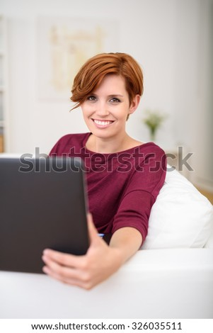 Attractive Young Woman Smiles at the Camera While Working on her Laptop Computer at the Living Room Couch.