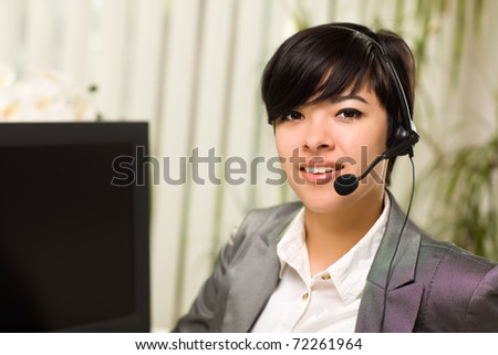 Attractive Young Woman Smiles Wearing Headset Near Her Computer Monitor. - stock photo