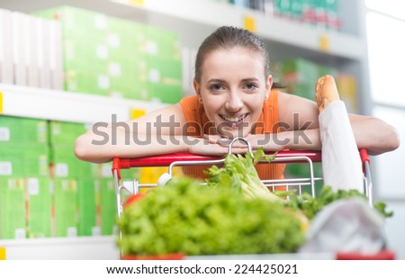 Attractive young woman smiling and leaning on shopping cart at supermarket. - stock photo