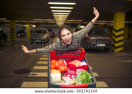Attractive young woman smiling and pushing a shopping cart at supermarket parking lot.Concept of sale,discount,low prices.Happy customer satisfied with offer.Trolley full with variety of products - stock photo