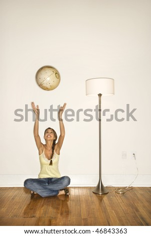 Attractive young woman smiling and sitting on the floor next to a floor lamp. She is tossing a globe into the air. Vertical shot. - stock photo