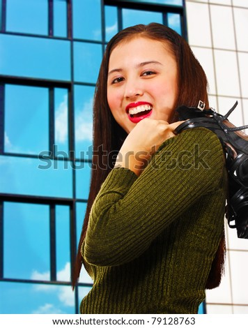 Attractive young woman smiling and standing in front of a reflective office building - stock photo