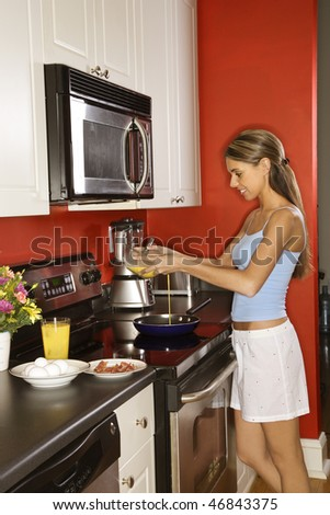 Attractive young woman smiling in her kitchen while cooking breakfast. She is dressed in sleepwear. Vertical shot. - stock photo
