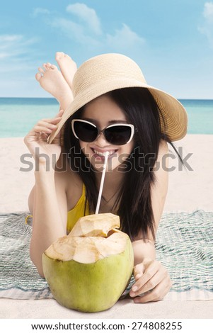 Attractive young woman smiling on the camera while drinking coconut water on the beach - stock photo