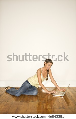 Attractive young woman smiling towards the camera and sitting on the floor with a laptop. Vertical shot. - stock photo
