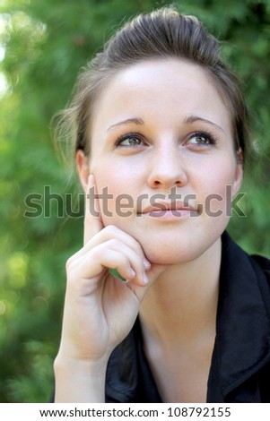 Attractive Young Woman Smiling While Thinking - stock photo