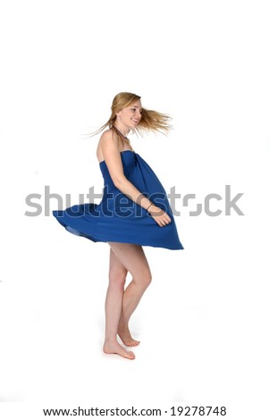 attractive young woman spinning around in a blue dress - stock photo
