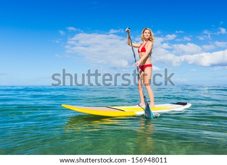 Attractive Young Woman Stand Up Paddle Surfing In Hawaii, Beautiful Tropical Ocean, Active Beach Lifestyle - stock photo