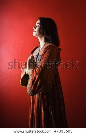 Attractive young woman standing against a red wall with hands held in prayer and eyes closed. Vertical shot. Isolated on red.