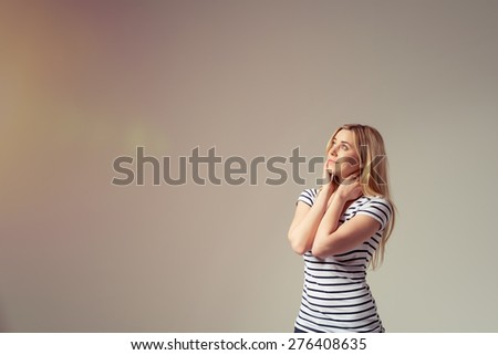Attractive young woman standing daydreaming with her hands clasped to her neck staring off into the distance with a serious expression, on grey with copyspace - stock photo