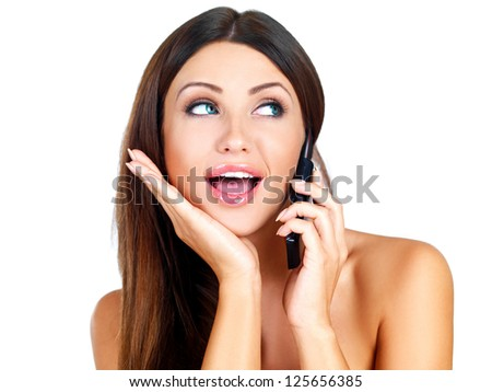 Attractive young woman standing gossiping on her mobile phone with her eyes raised looking to the side isolated on white - stock photo
