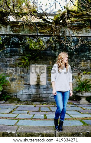 attractive young woman standing in concrete park