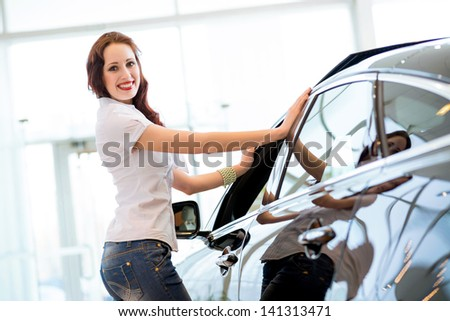 attractive young woman standing near a car in a showroom, chooses a car to buy - stock photo