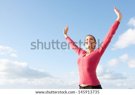 Attractive young woman standing with her arms outstretched up in the air above her head, joyfully smiling against an intense blue sky during a sunny day. - stock photo