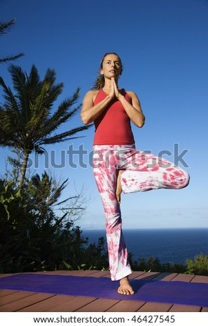 Attractive young woman stands on one foot doing the yoga tree pose with the ocean in the background. Vertical shot. - stock photo