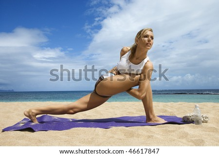 Attractive young woman stretches while doing yoga. She is on a sandy beach with the ocean in the background. Horizontal shot. - stock photo