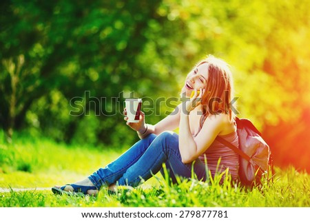 Attractive young woman talking by phone and holding cup of coffee outdoors. Sitting at the grass in park. Casual outfit, backpack. Sun lens flare. - stock photo