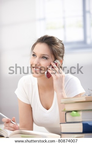 Attractive young woman talking on mobile phone, laying on floor, smiling.? - stock photo