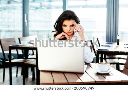 Attractive young woman talking on the phone and checking a website - stock photo