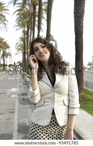 Attractive young woman talking on the phone in a tree aligned street. - stock photo