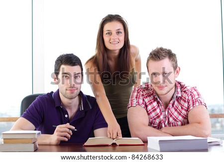 Attractive young woman teaches two young students