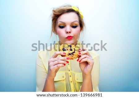 Attractive young woman tempted to eat a chocolate chip cookie - stock photo
