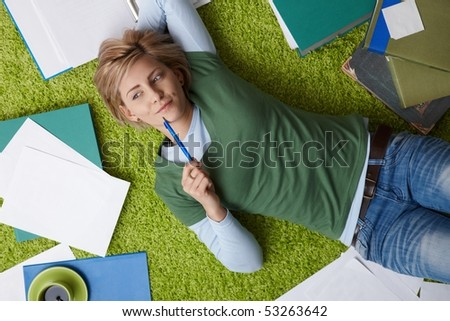 Attractive young woman thinking on floor, looking aside, pen in hand, surrounded by books and notes.