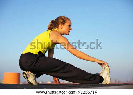 Attractive young woman traceur doing stretching exercises on an urban rooftop before participating in parkour - stock photo