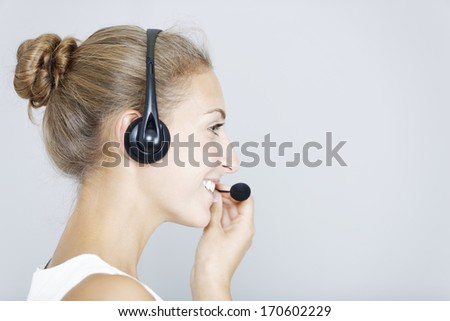 Attractive young woman using a telephone headset - stock photo