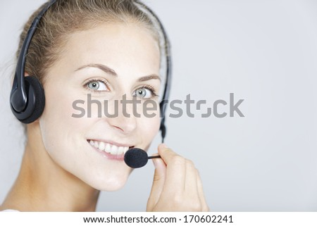 Attractive young woman using a telephone headset