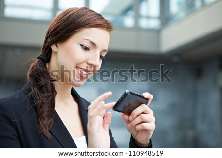 Attractive young woman using her smartphone on the way in the city - stock photo
