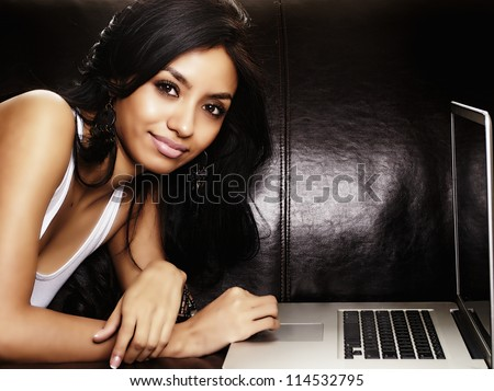 Attractive young woman using laptop computer - stock photo