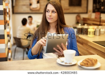 Attractive young woman using tablet computer in cafeteria, looking away. - stock photo