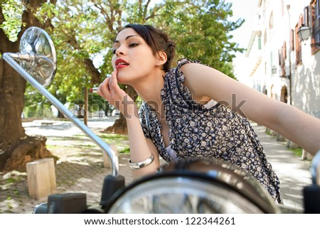 Attractive young woman using the mirrors on her motorbike to apply red lipstick on herself on a sunny day, outdoors. - stock photo