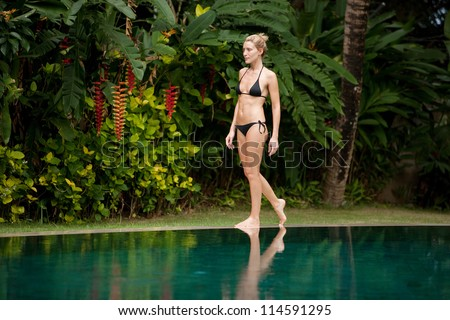 Attractive young woman walking along the edge of a swimming pool in a tropical garden with flowers. - stock photo