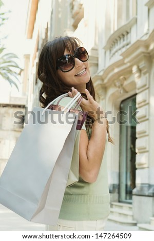 Attractive young woman walking down a shopping street in a classic city, holding shopping bags and turning around to smile at the camera. - stock photo