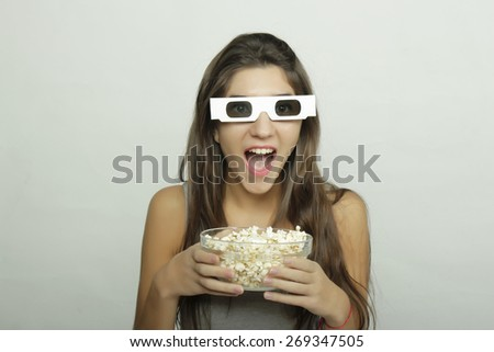 Attractive young woman watching a movie with popcorn and 3D glasses. Cinema concept - stock photo