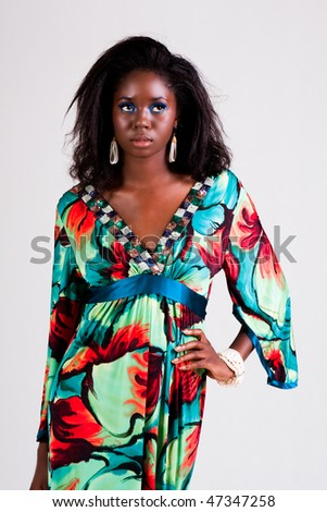 Attractive young woman wearing a colorful print dress and standing with one hand on her hip. Vertical shot. - stock photo