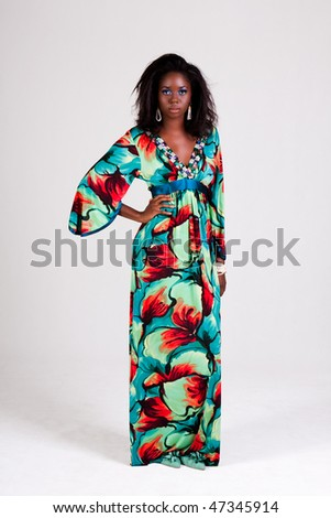 Attractive young woman wearing a colorful print dress. She is standing with one hand on her hip and looking back towards the camera. Vertical shot. - stock photo