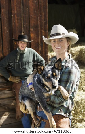 Attractive young woman wearing a cowboy hat and holding an Australian Shepherd. A young man is standing in the background. Vertical shot. - stock photo