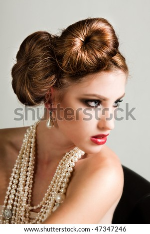 Attractive young woman wearing a pearl necklace and earrings. Horizontal shot. - stock photo