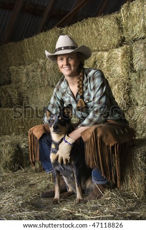 Attractive young woman wearing a white cowboy hat. She is sitting on hay and smiling while holding an Australian Shepherd. Vertical shot. - stock photo