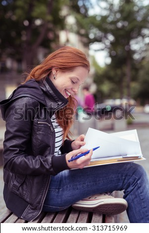 Attractive Young Woman Wearing Casual Winter Outfit, Studying her Lessons at the Outdoor Bench with happy Facial Expression. - stock photo